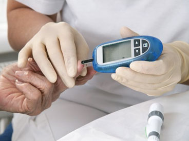 Nurse with latex gloves administering a diabetes blood test