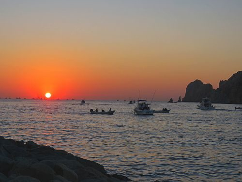A group of fishing boats out to sea at dawn.