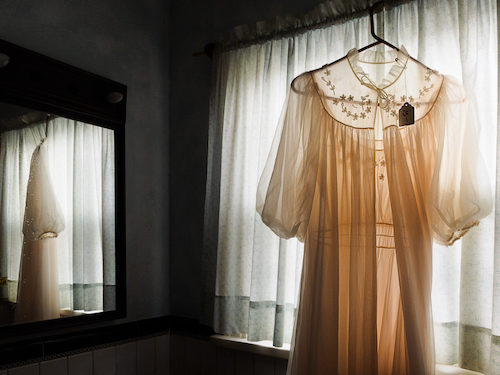 A pink negligee hangs on a curtain rod in a darkened room