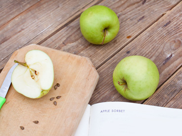 3 apples, cutting board, and cookbook