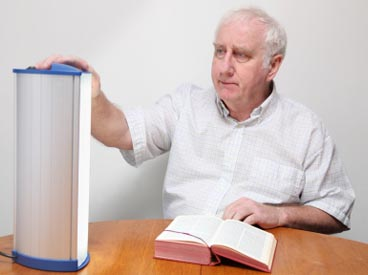 Elderly man using a light therapy lamp to treat SAD.