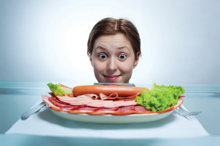 Girl staring at plate of meat