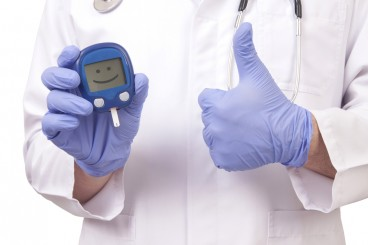 doctor holding glucose monitor with a smiley face on it