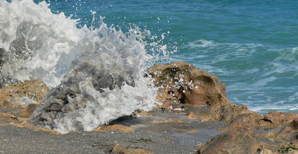 Ocean breaking on rocky shore at Blowing Rocks Preserve in Florida